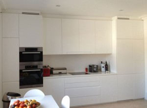 Kitchen with handle recesses. Birch plywood carcases and drawers. Exterior spray-painted in a matt pigmented white lacquer.  White Corian worktop with integral white splashback.