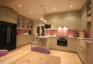 Hand-painted Kitchen with painted glass splashback and stone worksurfaces.