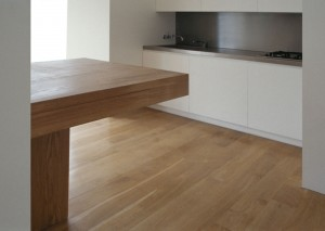 White lacquered kitchen with stainless steel worktop and integral splash-back.  Island unit made from Oak.