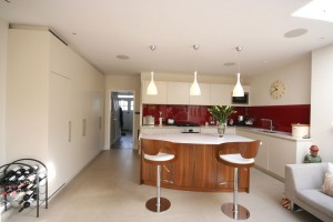 Spray-painted Kitchen with Walnut Island unit.  Composite stone worktops with striking red glass splash-backs.