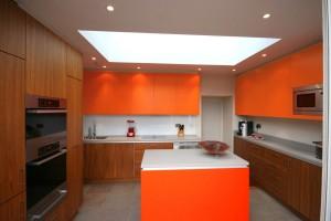 Walnut Kitchen with striking orange wall units.