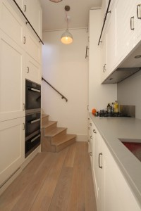 Small Kitchen with high ceiling space made with European Oak Carcases and hand-painted doors and exteriors.  Tarnished brass ladder rail and Oak Ladder.  Corian worksurface and integral splashback.