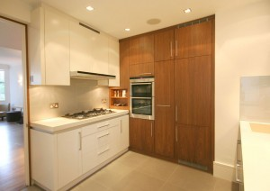 Kitchen made from a combination of spray-painted and Walnut veneered cabinets. Stone worksurfaces and neutral glass splashback.