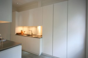 White lacquered Kitchen with handle groove detailing.  Glass splash-backs and stainless steel worksurfaces