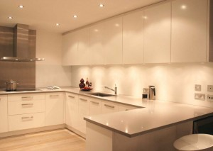 Gloss white lacquered Kitchen with white glass splash-backs and stone worksurfaces.