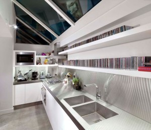 White lacquered Kitchen with handle groove detailing, integral under-shelf lighting.  Stainless steel worksurfaces and splashbacks.