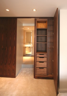 Bedroom Wardrobes with American Walnut interior and Santos Rosewood exterior.  'Jib' door through to en-suite bathroom.