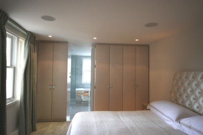 Bedroom Wardrobes with American Walnut interior and fabric covered doors.  'Jib' door through to en-suite bathroom.