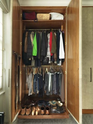 Wardrobe interior with pullout base and tarnished brass hanging rails.
