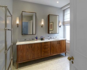 Walnut Vanity unit with two basins and stone top.  Wall cabinets made from Walnut with tarnished brass door frames surrounding bevelled mirrors.