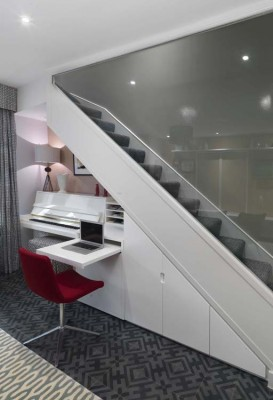 Understairs storage and occasional work area in a white lacquered finish.