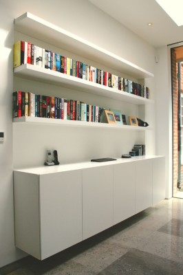 Spray-painted Wall-hung Media unit with 'floating' shelves with integral lighting above.