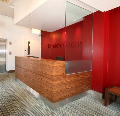 Reception Desk made from American Black Walnut veneer with stainless steel plinth and glass panel.