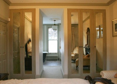 Wardrobes separating Bedroom from en-suite Bathroom.  Spray-painted interiors, bevelled antique mirror door panels and paint-effect exteriors.