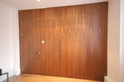 Walnut veneered wall of cabinets with 'Jib' door leading from room.