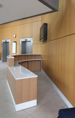 Reception Desk made from Quarter sawn European Oak veneers and composite stone top for the centre court reception at the New England Tennis and Croquette Club.  Designed by Opus Magnum.