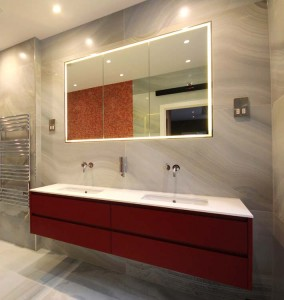 Red lacquered vanity unit with recessed mirror door wall cabinet with concealed perimeter lighting.