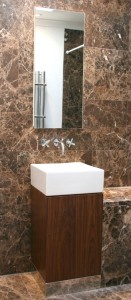 Walnut washbasin stand with polished stainless steel plinth.  Recessed mirror door wall cabinet.